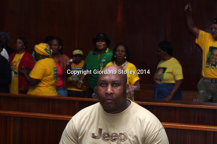 DURBAN - 25 September 2014, Former Blue Bulls rugby player Phindile Joseph Ntshongwana who stands accused of killing four people with an axe, trying to kill two others, raping another and assaulting  another person sits in the dock in the Durban High Court before Acting Judge Irfaan Khalil continued delivering his judgement. In the background are supporters of the African National Congress who were singing songs calling for justice. Picture: Allied Picture Press/APP