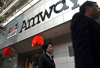 People walk past a branch of the US direct sales company Amway in Nanchang, Jiangxi province, China.  .08-FEB-03