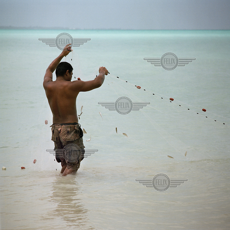 A young fisherman looks at his meagre catch in the net while reef fishing in the lagoon.