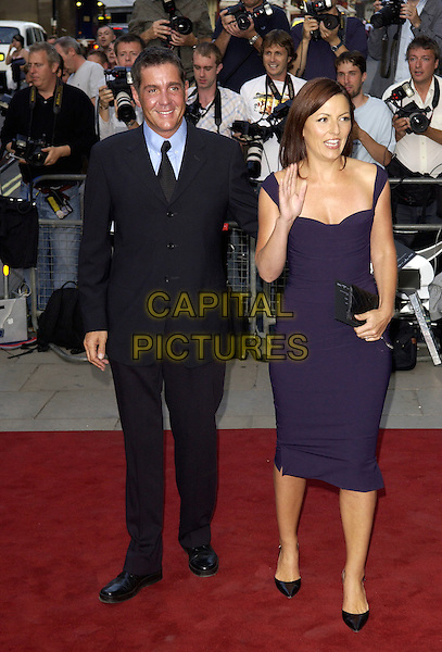 DALE WINTON & DAVINA McCALL.GQ Men Of The Year Awards at the Royal Opera House, Covent Garden, London, WC2..September 6th, 2005.full length black suit purple dress black clutch purse waving.www.capitalpictures.com.sales@capitalpictures.com.© Capital Pictures.