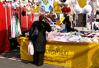 Vrouw staat bij een lingeriekraam op de Dappermarkt in Amsterdam