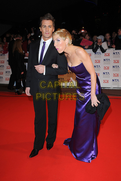 MATT EVERS & HEATHER MILLS.Arrivals at the 15th National Television Awards held at the O2 Arena, London, England. .January 20th, 2010 .NTA NTAs full length black suit tie strapless purple maxi dress clutch bag bending leaning funny profile .CAP/BEL.©Tom Belcher/Capital Pictures