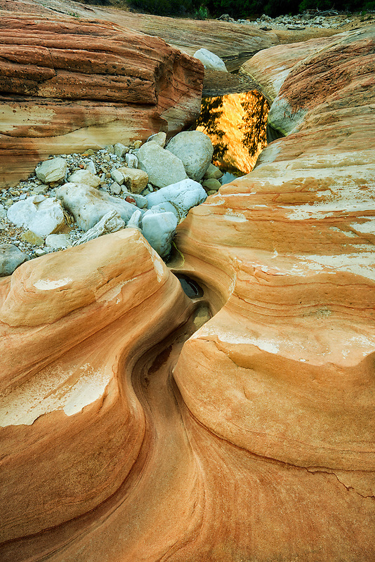 Sandstone rock formation with pool of water reflecting mountains. Zion National Park, Utah