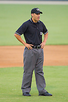 Umpire Derek Mollica handles the calls on the bases during a South Atlantic League game between the Hickory Crawdads and the Kannapolis Intimidators at Fieldcrest Cannon Stadium August 17, 2010, in Kannapolis, North Carolina.  Photo by Brian Westerholt / Four Seam Images