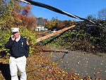 South Windsor Fire Chief Phillip E. Crombie, talks on his cell phone dealings with almost contest stream of phone calls dealing with the aftermath of the snowstorm, Friday, Nov.4, 2011, on Scott Drive in South Windsor. Trees down in the roadway tangled in power lines has made 35 streets in town impassible for emergency vehicles. Police Chief Matthew Reed and Crombie went public Friday concerning CL+P's lack of response to repeated requests to get the trees removed from wires saying they will hold the company responsible for any fire deaths, injuries or property damage in those sections of town that remain inaccessible. (Jim Michaud/Journal Inquirer)