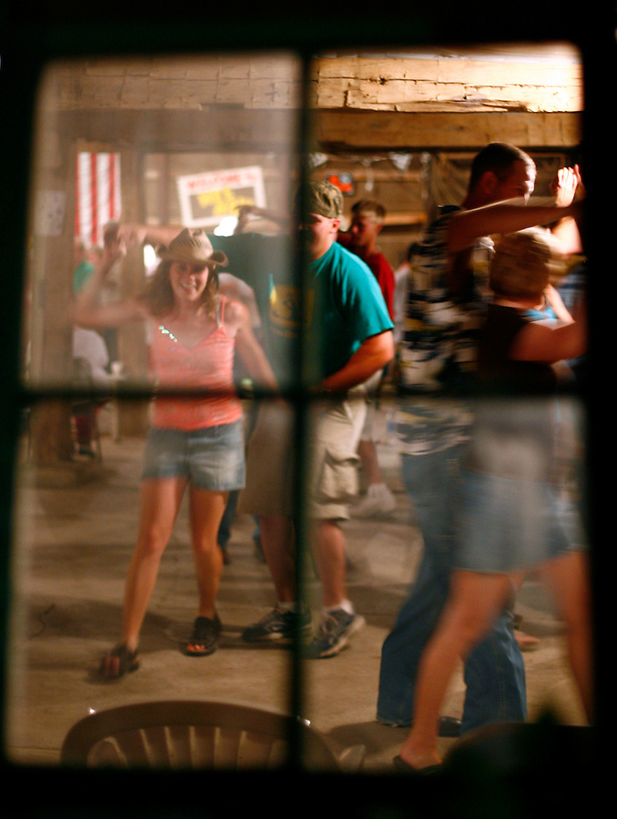 Square dancers are seen through a window of the barn as they dance late into the night.<br />