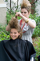 Young girl age 10 having a buzz style in outdoor beauty shop. Grand Old Day Street Fair St Paul Minnesota USA