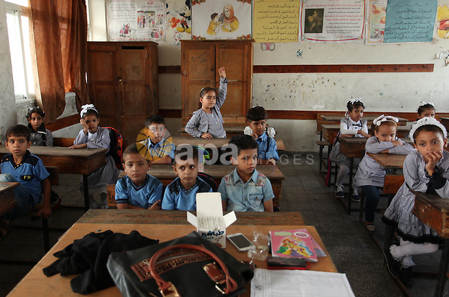 Palestinian schoolchildren attend a lesson in a classroom on the first day of a new school year, at a United Nations-run school in Khan Younis in the southern Gaza Strip August 28, 2016. Photo by Ashraf Amra