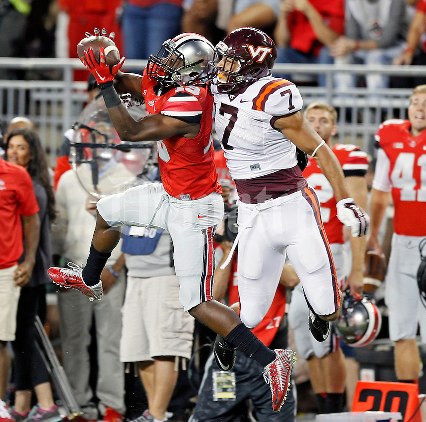 Ohio State Buckeyes cornerback Eli Apple (13) makes an interception against Virginia Tech Hokies tight end Bucky Hodges (7) during the 1st quarter of their game in Ohio Stadium on September 6, 2014.  (Dispatch photo by Kyle Robertson)