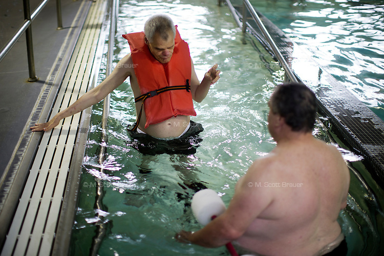 Mike Hebert helps Fernald Developmental Center resident Ronnie Russo (vest) walk in the pool at the Fernald Center Aquatics pool in the Green Building at Fernald in Waltham, Mass., USA. The twins Ronnie and Randy Russo go to the pool twice a week and, with help from Hebert, walk around the pool with light water weights as a way to get exercise and maintain limb strength.  Hebert was an employee at Fernald, but now volunteers as a swim tutor with the twins twice a week.