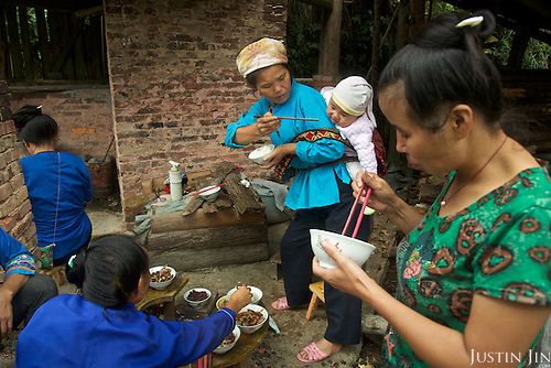 A grandmother feeds a child in Dimen.