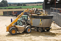 JCB loading silage into a Shelbourne Powermix Pro mixer waggon for feeding to dairy cattle.