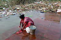 A woman cleans clothes on the banks of the Ganges River in Kolkata.<br />