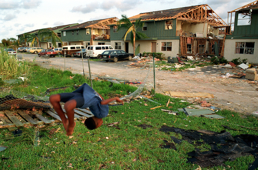 "Kentereon ""Squiggy"" Hollowell turns a back flip in front of the remains of the Sea Grape Village apartments where he lived before the storm. The government-subsidized housing in Homestead was condemned, leaving hundreds of residents in need of new homes."