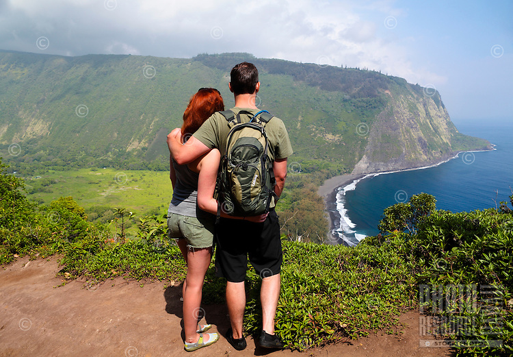 Hikers look at historic and sacred Waipi'o Valley along Hamakua district's coastline, Big Island.
