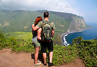 Hikers look at historic and sacred Waipi'o Valley along Hamakua district's coastline, Big Island.