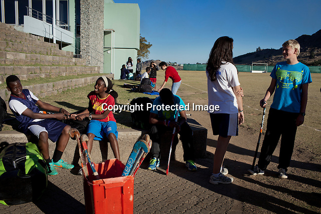 MBABANE, SWAZILAND - AUGUST 1: Students socialize before a hockey practice at Waterford Kamhlaba United World College of Southern Africa, a secondary school on August 1, 2013 in Mbabane, Swaziland. They have several sports fields and football, rugby, netball and volleyball is popular.  Many students are busy with sports, art, and music after school hours. (Photo by: Per-Anders Pettersson)