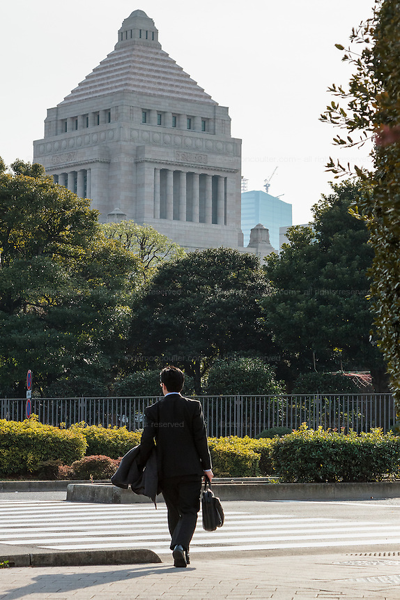 A Japanese office worker or salaryman crosses a road near the Japanese Diet (Parliament) Building, Nagatacho, Tokyo, Japan. Friday February 5th 2016