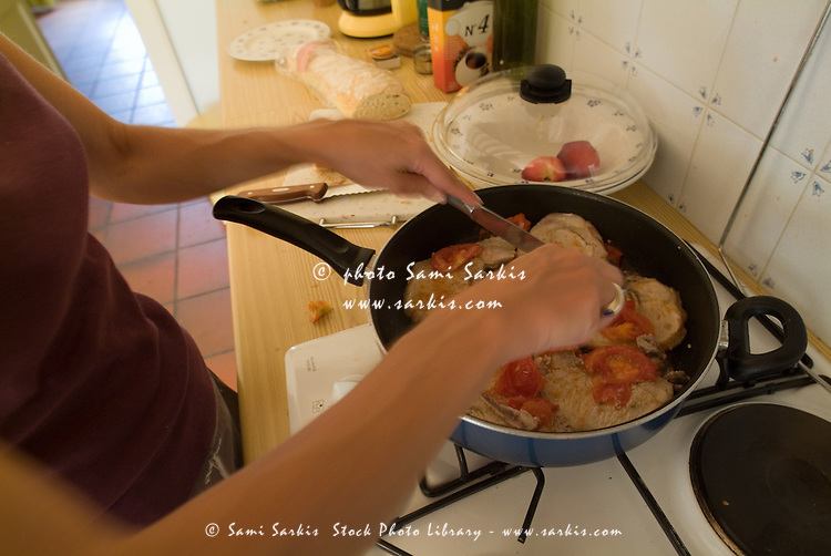 Hands of a woman cooking chicken and preparing food in a kitchen.