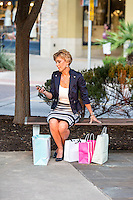 Attractive female shopper text on her smartphone at an Austin outdoor shopping mall