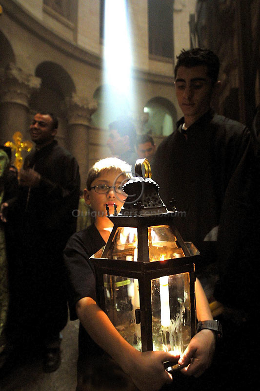 A Syrian Orthodox boy, holding a box with candles is illuminated by a sunray as he takes part of the Holy Fire ceremony in the Church of the Holy Sepulcher in Jerusalem, Saturday, May 4, 2002.