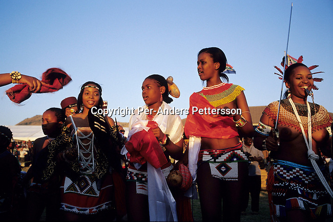 NONGOMA, SOUTH AFRICA - SEPTEMBER 11: Unidentified Zulu princesses dance at the Royal Palace during the annual Reed Dance on September 11, 2004 in Nongoma in rural Natal, South Africa. About 20.000 maidens from all over South Africa arrived to dance for Zulu King Goodwill Zwelethini at the Enyokeni Royal Palace in Kwa-Nongoma about 350 kilometers from Durban. The girls come to the kingdom to declare their virginity and the ceremony encourages girls and young women to abstain from sexual activity to curb the spread of HIV-Aids..(Photo: Per-Anders Pettersson)......