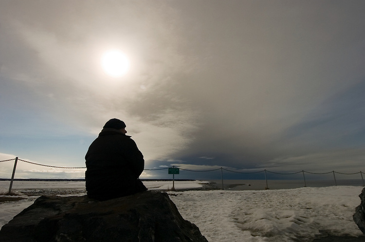 From a bluff at the mouth of the Kenai River in Kenai, Alaska, Ed Witveck watches an ash cloud from Mount Redoubt's March 26, 2009, eruption as it makes its way toward the southern Kenai Peninsula. The could climbed 12 miles into the sky during the event. .