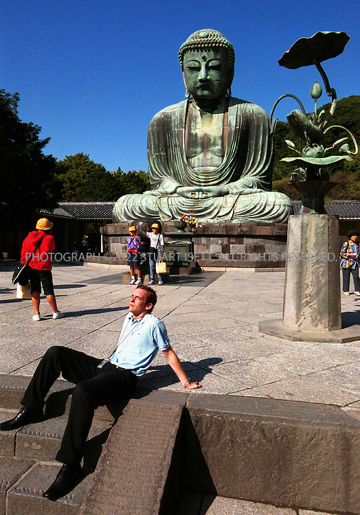 10/11/2001--Kamakura, Japan.Japanese and foreign tourists at Kamakura's famous Daibutsu (Great Buddha) built in 1252. Kamakura is a popular tourist site located just 45 minutes south of Tokyo...All photographs ©2003 Stuart Isett.All rights reserved.This image may not be reproduced without expressed