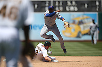 OAKLAND, CA - JUNE 18:  Elvis Andrus #1 of the Texas Rangers turns a double play at second base against the Oakland Athletics forcing out A's base runner Craig Gentry #3 during the game at O.co Coliseum on Wednesday, June 18, 2014 in Oakland, California. Photo by Brad Mangin