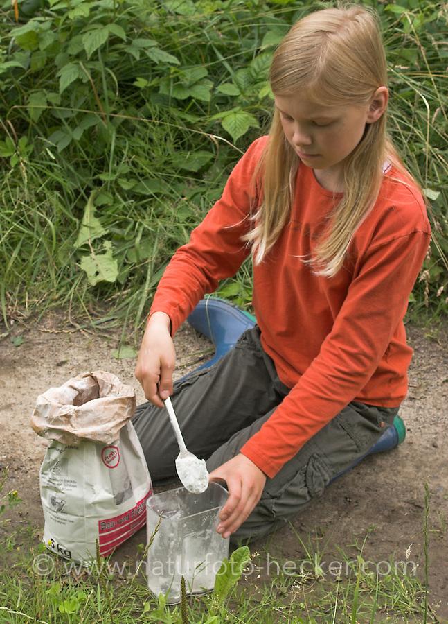 Kinder gießen Tierspur aus Gips, Mädchen füllt Gips in einen Messbecher