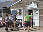 Queue of people outside the Company Shed fish restaurant, West Mersea, Mersea Island, Essex, England