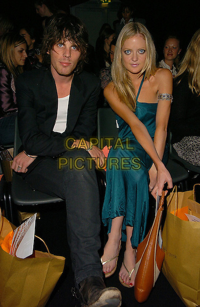 JACKSON SCOTT & GUEST.At The Gharani Strok Show, London Fashion Week,.London, 19th September 2005.full length seated sitting black jacket boots blue satin dress.Ref: CAN.www.capitalpictures.com.sales@capitalpictures.com.©Capital Pictures