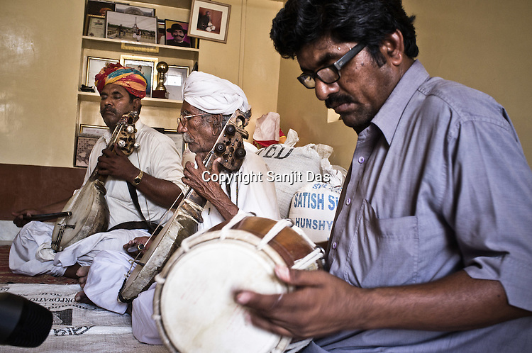 75-year-old Manganiyar artist, Saqar Khan plays his Kamancha (music instrument) while his two sons, Ghewar Khan (45, Left) and Firoze Khan (38, right) accompany him during field recordings inside their house in Hamira village of Jaiselmer district in Rajasthan, India. Photo: Sanjit Das/Panos