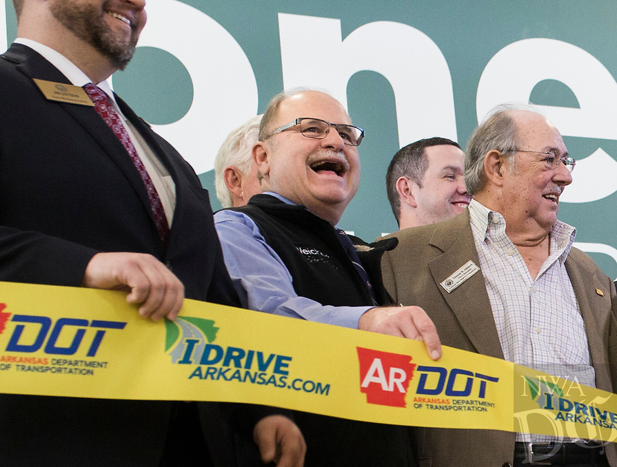 NWA Democrat-Gazette/CHARLIE KAIJO Arkansas Highway Commission member Philip Taldo (center) holds a ribbon also shown with Commission Chairman Tom Schueck (right) during a ribbon cutting, January 4, 2019 at the Jones Center in Springdale. <br />