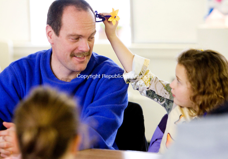 WOODBURY, CT- 06 JAN 2008- 010608JT01-<br /> Sharon McCarthy, 7, puts an origami flower behind her father David's ear during a program at Woodbury Public Library on Sunday in which Buddhist priest Brian Vaugh hosted a tea meditation followed by Sandy Carlson showing examples of origami paper folding.<br /> Josalee Thrift / Republican-American