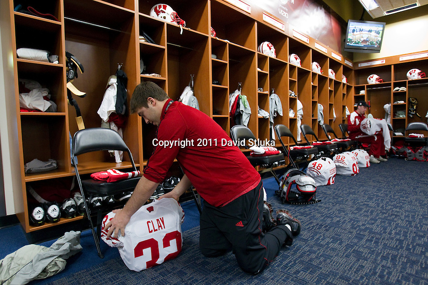 Wisconsin Badgers student manager Shane Baldauf puts the jersey of wide running back John Clay (32) on the shoulder pads prior to the 2011 Rose Bowl NCAA Football game against the TCU Horned Frogs in Pasadena, California on January 1, 2011. (Photo by David Stluka)