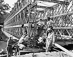Finishing touches are made on a Bailey Bridge at Platts Mills. The bridge is scheduled to be open for use tomorrow. Erected on the same site as the original span, the bridge has been constructed well above the level of the old bridge so that construction work on a new permanent span can be done under the Bailey. 18 September 1955.