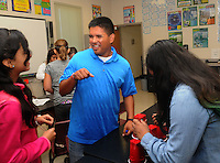 NWA Democrat-Gazette/FLIP PUTTHOFF <br /> Ryan Quintana, world history and science teacher at Lingle Middle School in Rogers, works Friday Sept. 23 2016 with students on a science project.