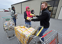 NWA Media/Michael Woods --12/17/2014-- w @NWAMICHAELW...Volunteers (left to right) Aaron Wilson, Tara Talbert and Brock Meadows, from Walmart, help give out food to local families Wednesday morning at the Salvation Army building in Springdale.  Several local volunteers helped distribute toys and food to local families for the holidays during the Salvation Army's annual event.
