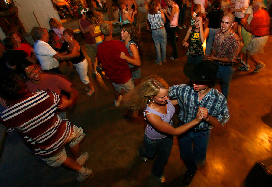 Christine and Jason Hoffman square dance with their friends during the Alles Barn Dance on Saturday night.<br />