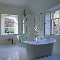 A large free-standing roll-top bath has views from the dual aspect windows in this large and light-filled bathroom
