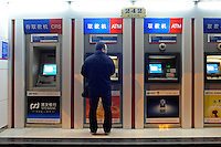 A man uses the ATM machine with SPD Bank on Nanjing Road, central Shanghai..