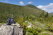 Hiker on the Zeacliff Trail in the White Mountains, New Hampshire during the summer months. Zeacliff Mountain is in the background. This area, near the Zeacliff Trail and Ethan Pond Trail junction, was part of the Zealand Valley Railroad (1885-1897).