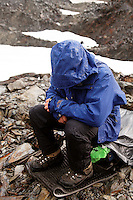 Man in alpine mountains sitting on backpack for protection during lightning storm, Bailey Range, Olympic Mountains, Washington