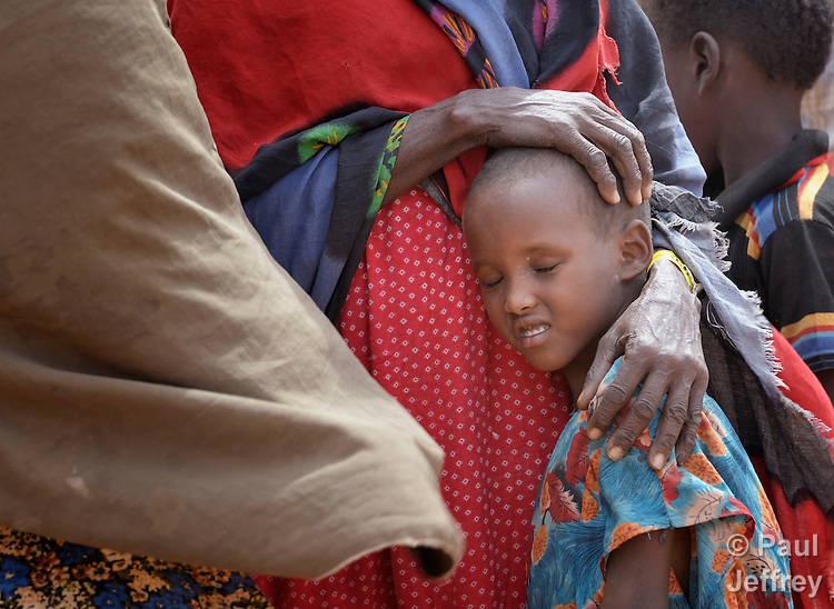 A newly arrived Somali refugee child rests on his mother while waiting to be registered in the Dadaab refugee camp in northeastern Kenya. Tens of thousands of newly arrived Somalis who have swelled the population of what was already the world's largest refugee camp.