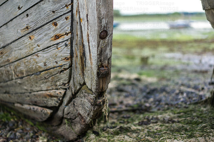 Close up of a large old wooden sailing boat abandoned on a muddy river bank in England