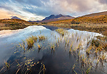 Isle of Skye, Scotland: Morning clouds clearing over the Cuillin mountains with reflections in a pond near Sligachan