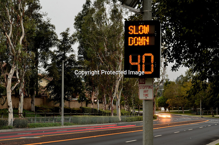 Cars speeding pass a traffic warning sign