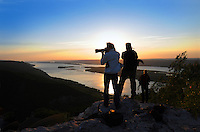 Silhouettes of photographers on top of Zhiguli mountains at sunset over Volga river