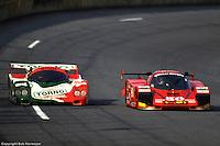 The Brun Motorsports Porsche 962 sweeps past the Alba AR6 Ferrari of Gaston Andrey Racing going through Daytona's tri-oval during the 1988 24 Hours of Daytona.